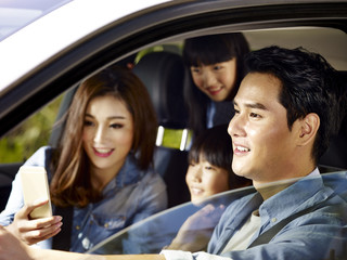 happy asian family traveling by car