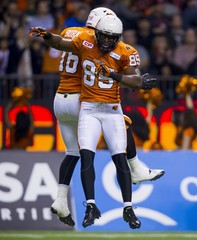 B.C Lions' Shawn Gore celebrates his touchdown against the Hamilton Tiger-Cats with team mate Bryan Burnham during their CFL football game in Vancouver
