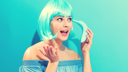 Wall Mural - Woman in bright blue wig holding blue banana