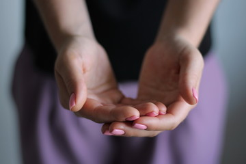 Young woman's hands keeps something. Gesture