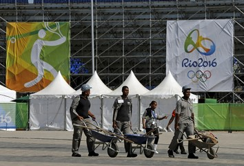 Workers are seen carrying tools in wheelbarrows next to the Tennis Stadium in Rio de Janeiro