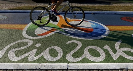 Woman rides her bicycle as she passes over a newly-painted bicyle lane ahead of the Rio 2016 Olympic games in Rio de Janeiro