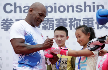 Former boxer Mike Tyson signs on a boxing glove for a student on the outskirts of Beijing