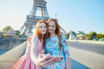Two friends taking selfie near Eiffel tower in Paris, France