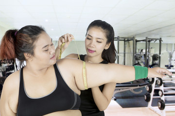 Instructor measuring arm of fat woman