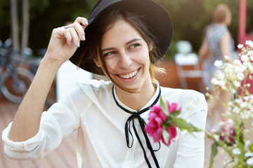 Outdoor portrait of young attractive woman in black hat and white blouse holding hand on hat sitting in cafe in open air smelling flowers smiling while looking aside enjoying good sunny weather