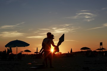 A cabana boy at the Sands Beach Club is seen as he takes down a beach umbrella at sunset on the beach in Atlantic Beach, New York