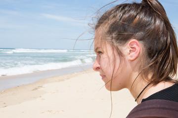 cheerful profile girl sad on beach alone