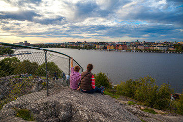 Tourists couple in Stockholm enjoying cityscapes of old town from rock