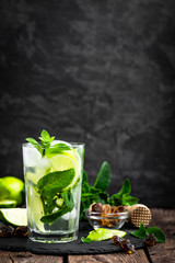 Refreshing mint cocktail mojito with rum and lime, cold drink or beverage with ice on black background