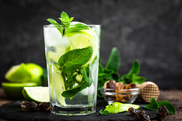 Acrylic Prints Cocktail Refreshing mint cocktail mojito with rum and lime, cold drink or beverage with ice on black background