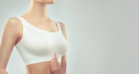 Body of a woman in the white top with the beautiful shape of the breast. Healthy Breasts . Medicine,sport and fitness .