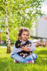 Little girl with a berner sennenhund puppy, outdoor, summer