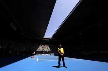 A security guard stands on court as the roof of Rod Laver Arena opens at the Australian Open tennis tournament at Melbourne Park, Australia