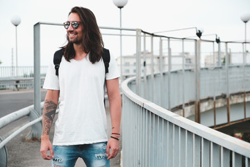 Stylish hipster model with long hair lifestyle in the street. Dressed in a white T-shirt and torn blue jeans in the city