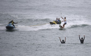 Brazilian surfer Rico de Souza carries the Olympic torch as he surfs at praia da Macumba (Macumba beach) in Rio de Janeiro