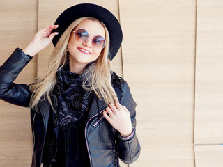 Funny and beautiful blonde in sun glasses and a hat. Trendy girl portrait outdoor. Holds hat