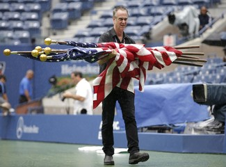 A worker removes American flags from courtside as rain delays the start of the men's singles final match between Federer of Switzerland and Djokovic of Serbia at the U.S. Open Championships tennis tournament in New York