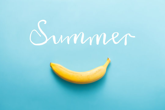 Fresh juicy banana on blue painted wooden background with white handwriting
