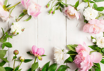 Pink and white flowers on wooden table. Wreath made with peonies and wild roses. High key, copy space.