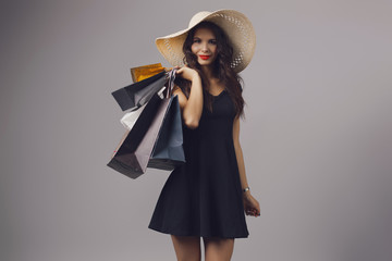 Brunette young woman in elegant black dress and summer hat. Girl posing on a studio background. Fashion photo