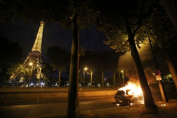 Flames from a burning car is seen near the Eiffel Tower during a EURO 2016 final soccer match