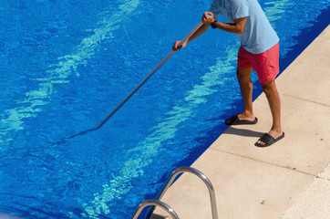 Man cleaning the swimming pool with a telescopic pole