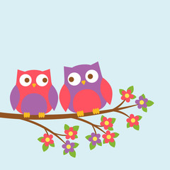 Couple of cute owls on blooming branch
