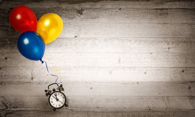 Clock flying with several balloons on a wooden background