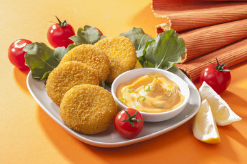 Chicken and cheese fried tikki with lemon and cherry tomato on orange background