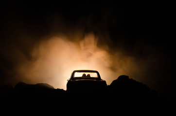 silhouette of car with couple inside on dark background with lights and smoke. Romantic scene. Love concept
