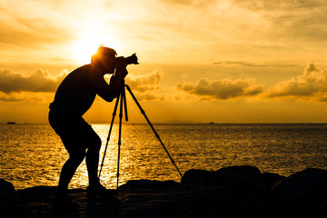 Silhouette of man taking photo with tripod