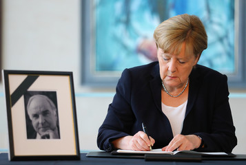 German Chancellor Merkel writes a message in a book of condolence for former German chancellor Kohl at the Chancellery in Berlin