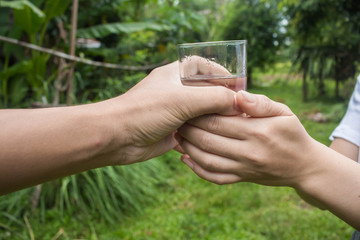 Man hand giving glass of fresh water to women in the park.