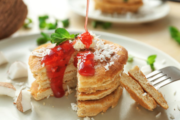 Tasty homemade coconut pancakes with berry sauce on plate
