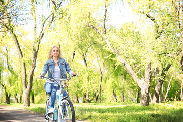 Happy young girl on bicycle riding in park