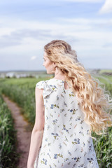 Summer portrait of beautiful blonde lady in wheat field
