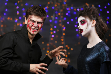 Young man and woman with Halloween makeup at party