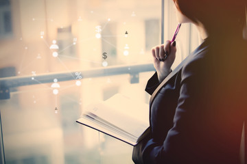 young beautiful woman holding a notebook and thinking near the window