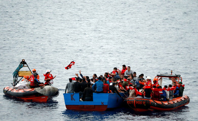 """Migrants on a wooden boat are rescued by """"Save the Children"""" NGO crew from the ship Vos Hestia in the Mediterranean sea off Libya coast"""
