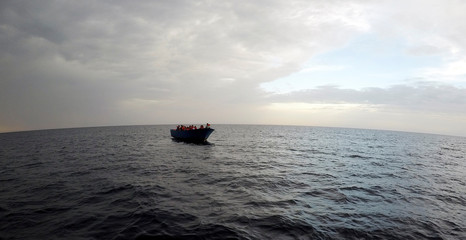 """Migrants on a wooden boat wait to be rescued by """"Save the Children"""" NGO crew from the ship Vos Hestia in the Mediterranean sea off Libya coast"""