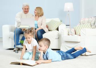 Grandchildren looking through photo album at home