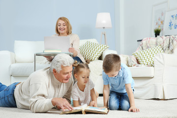 Grandchildren with grandfather looking through photo album at home