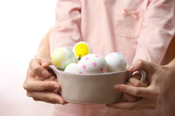 Woman and cute child holding bowl with Easter eggs, closeup