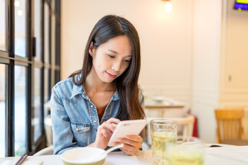 Woman use of mobile phone in chinese restaurant