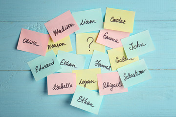Paper stickers with different names on color wooden background. Concept of choosing baby name