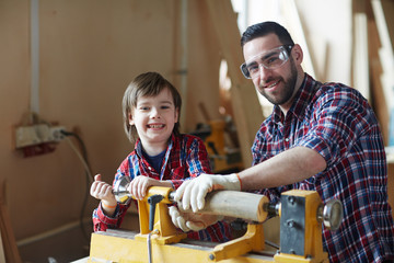 Boy and his father standing by woodworking machine in workshop