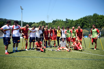 Spain's and Brazil's national team amputee football players pose for a picture following a tournament match to promote the sport known as OneFoot-Ball, in Zubieta
