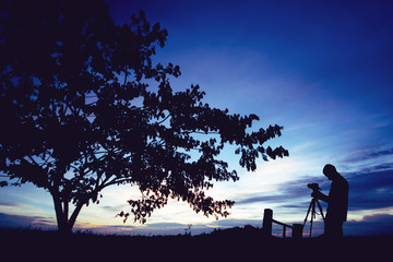 Silhouette photographer with camera on tripod taking pictures of nature tree on sunset.