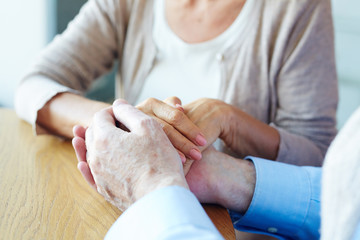 Hands of senior couple on wooden table